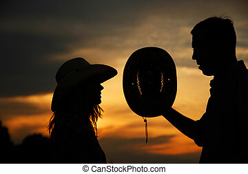 young couple in love silhouette in cowboy hats - a young...