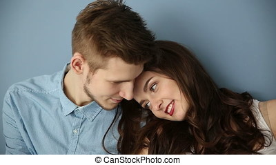 Young couple in love sitting at home by the blue wall - dolly shot