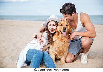 Young couple in love sitting on the beach with dog