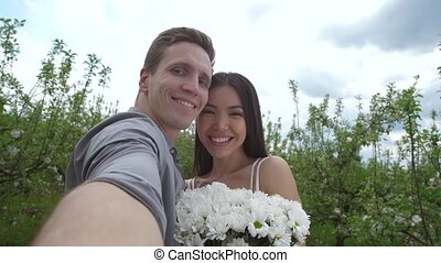 Young couple in love taking selfie dating outdoors