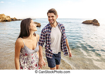 Young couple in love walking at the beach holding hands