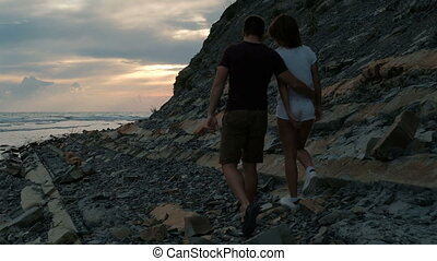Young couple in love walking in evening on a rocky beach.