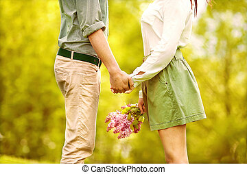 Young couple in love walking in the park holding hands looking in the sunset