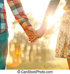 Young couple in love walking in the autumn park holding hands lo