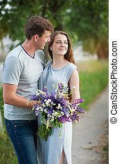 young couple in love with a bouquet of flowers on a background of the path