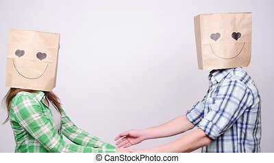 Young couple in love with bags over heads on gray background