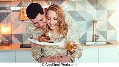 young couple in morning with pancakes - Happy cheerful...
