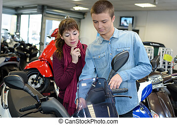 Young couple in motorcycle showroom