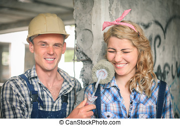 Young couple in overalls with roller for painting. Concept of construction and home repair.