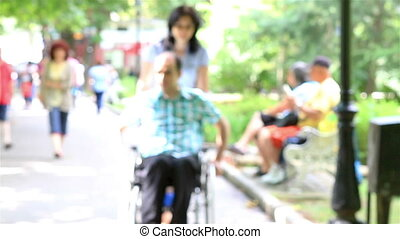 Young couple in park. Her husband is in wheelchair.