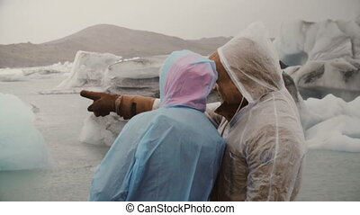 Young couple in raincoat exploring the famous sight - ice lagoon in Iceland. Tourist man show something to woman.