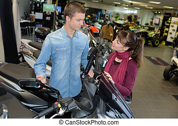 Young couple in scooter showroom