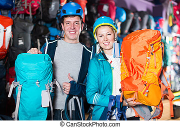 Young couple in shop chooses backpacks