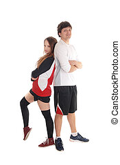 Young couple in sportswear standing back to back