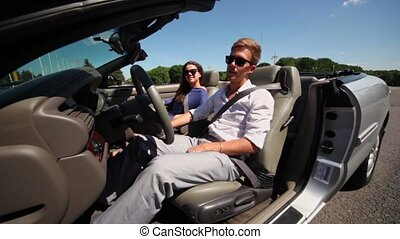 couple in sunglasses sit in cabriolet with driver door open...