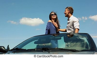 Young couple in sunglasses stand on cabriolet and look at sun