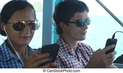 Young couple in sunglasses traveling by ship. They sitting on the deck and use mobile phone. slow motion. 1920x1080