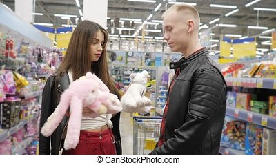 Young couple in supermarket is choosing teddy toy - pink...