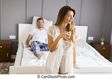 Young couple in the bedroom, woman drinking water and a man lying on the bed