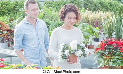 Young couple in the greenhouse. - Happy couple. Lovely young...
