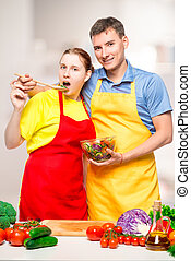 young couple in the kitchen posing with vegetable salad in a bowl