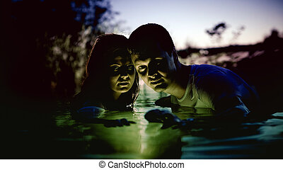Young couple in the magic luminous river on the summer...