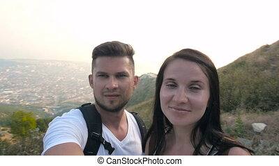 Young Couple In The Mountains With Backpacks Makes Selfie Summertime Evening
