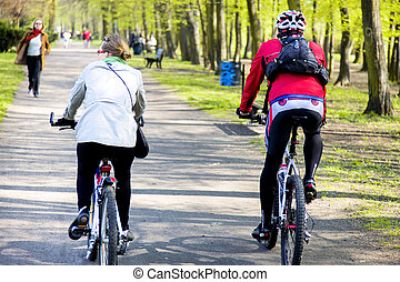 Young couple riding bikes in the spring Park