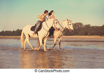 Young couple in the sea on horseback