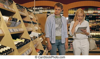 Young Couple In The Store Checking List of Products on Tablet PC And Taking Two Bottles of Wine