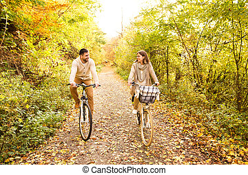 Young couple in warm clothes cycling in autumn park. -...