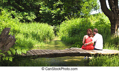 Young couple inlove sitting on a bridge