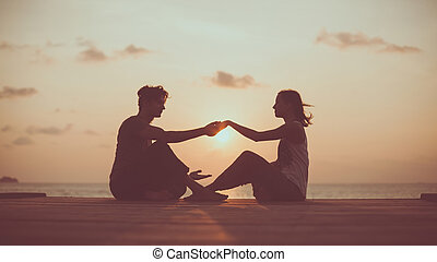 Young couple is doing yoga on the sunrise background.