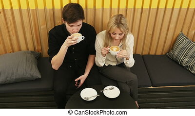 Young couple is drinking coffee and talking while sitting at the cafe