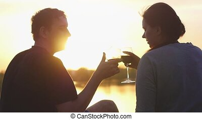 Young couple is drinking wine by the sea at sunset. They sit on the sand, clink glasses in slow motion. Anniversary or honeymoon. 1920x1080