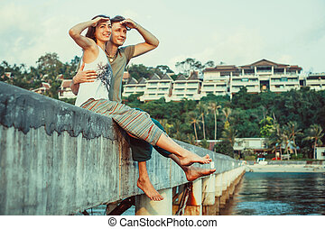 Young couple is relaxing on the pierce watching the sea.