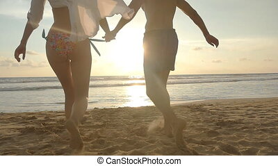 Young couple is running on the beach, man hug and spin around his woman on sunset. Girl jumps into her boyfriend arms, he whirling her at beautiful seaside. Having fun together at vacation. Slowmotion