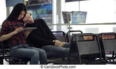 Young couple is sitting in airport waiting area.
