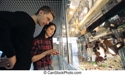 Young couple is watching souvenirs in airport shop.