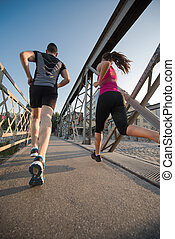 young couple jogging across the bridge in the city