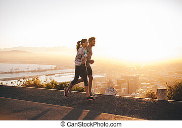 Young couple jogging on hillside road - Shot of young couple...