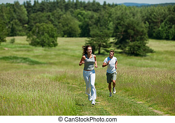 Young couple jogging outdoors in spring nature