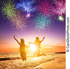 young couple jumping on the beach with fireworks background