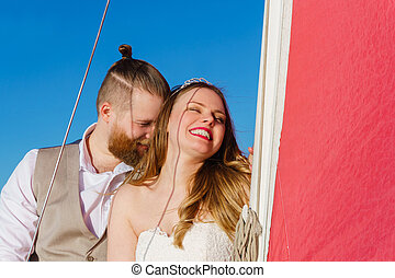 young couple just married on a sailboat