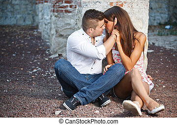 Young couple kissing against brick frame building