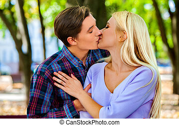 Young couple kissing and flirting in  park.