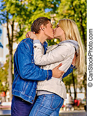 Young couple kissing and hugging in  park.