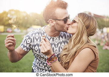 Young couple kissing at music festival