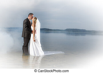 Young couple kissing by the lake