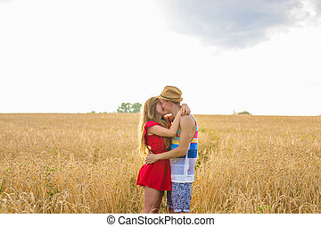 young couple kissing in a field. Young woman hugging a caucasian man in the middle of a wheat field and kissing each other. concept about passion and love
